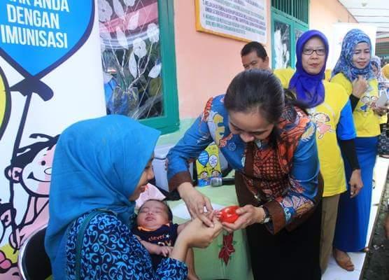Hj. Shinta Muzakir saat memberikan imunisasi polio kepada salah seorang balita